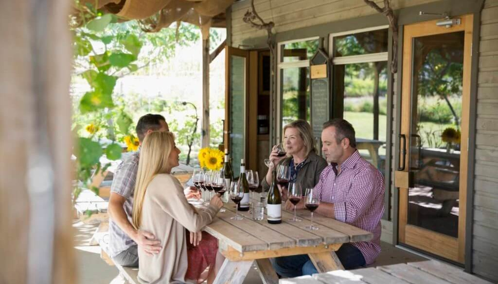 Couples wine tasting drinking red wine on patio at winery tasting room